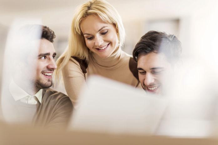 Drei moderne Geschäftsleute mit Laptop gemeinsam im Büro.